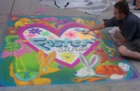 "Roger Whiting painting a chalk mural of a heart with ""Foster Care"" written on the inside"